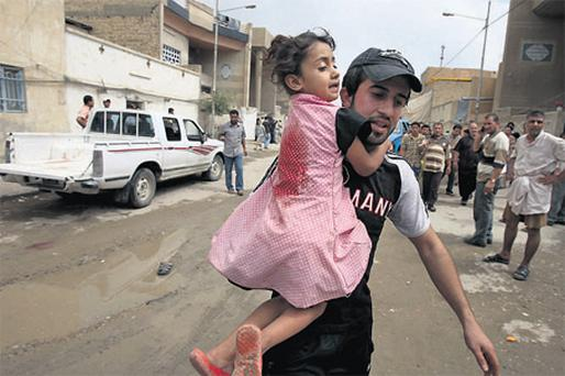 A man carries an injured girl after a series of parked car bombs exploded in the Shia stronghold of Sadr City in Baghdad yesterday