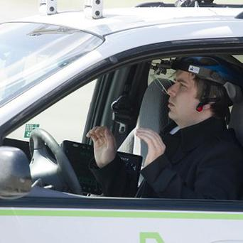 Scientist David Latotzky sits in a car, turning the steering wheel with his eye movements