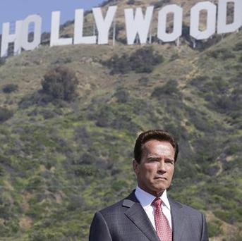 California Governor Arnold Schwarzenegger joins a news conference under the Hollywood sign
