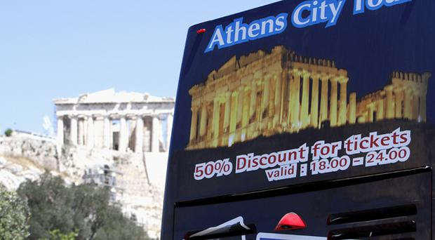 A banner advertises discounts on city tours in Athens. Photo: Bloomberg News