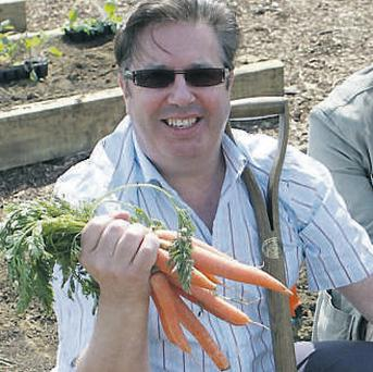 Gerry Ryan poses with a bunch of carrots last week on a visit to his radio show's garden in the RTÉ campus at Donnybrook