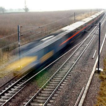 A railway buff filming a steam train narrowly avoided being hit by an express