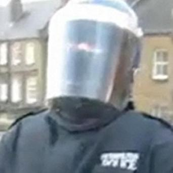 An image taken from a Youtube video of a man wearing a police riot helmet encouraging friends to shoot him with a toy gun