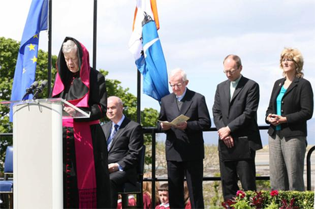 The wind plays a trick on Archbishop Michael Neary as he prays for the victims