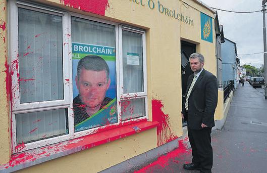 Green Party Senator Niall O'Brolchain assesses the damage after paint was thrown over his Galway office