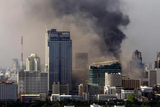 BANGKOK, THAILAND - MAY 19:A general view of the Bangkok Skyline show smoke rising into the air following a crackdown by Thai security forces on the Red shirt protesters' camp on May 19, 2010 in Bangkok, Thailand. At least 5 people are reported to have died as government forces sought to overrun barricades raised in and around the city centre by anti-government protestors. Red-shirt leaders have now surrendered, ending their blockade in the aftermath of a sixth day of violence, leaving the army in control and a night time curfew to be imposed. (Photo by Athit Perawongmetha/Getty Images)