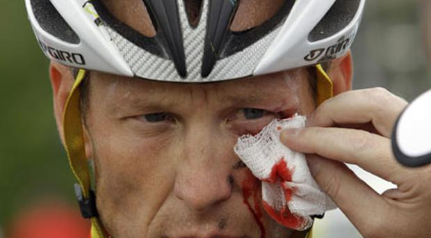 Lance Armstrong is tended to after crashing during the Tour of California yesterday after dismissing doping allegations from Floyd Landis. Photo: Associated Press