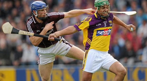 Wexford's Keith Rossiter tries to escape from the clutches of Galway's Cyril Donnellan (left) on Saturday evening.