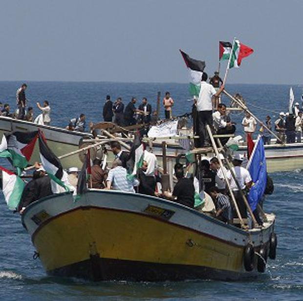 Palestinians ride boats in Gaza waters as a flotilla of aid ships leaves for the blockaded territory (AP)