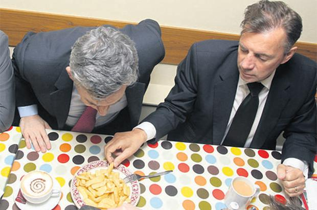 Businessman Duncan Bannatyne takes a chip from the plate of former prime minister Gordon Brown in a fish and chip shop in Great Yarmouth during a stopover in last month's UK election campaign
