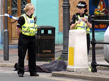 Police stand next to a body covered by a blanket following a shooting on Duke Street, Whitehaven, Cumbria. Photo: PA