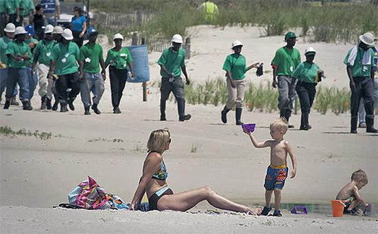 Mary Smith plays with her grandsons beside workers contracted to clean oil from the Deepwater Horizon oil leak that washed ashore in Alabama