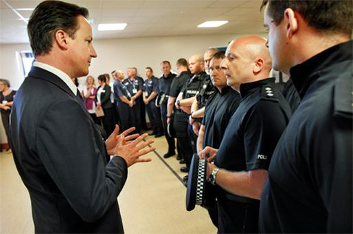 Britain's prime minister David Cameron meets senior police officers in Workington, England, yesterday
