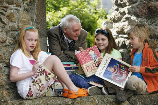 Participating Author Eamon Dunphy reading to local kids Sally Heneghan (10), Lucy McWilliams (10), and Calvin Gallardo-Kinlay (7) while kicking-off the Dalkey Book Festival in Dalkey Castle