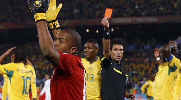 Referee Massimo Busacca of Switzerland shows the red card to Itumeleng Khune after the South African' keeper gave away a second-half penalty which was converted by Uruguay's Diego Forlan. Photo: Reuters