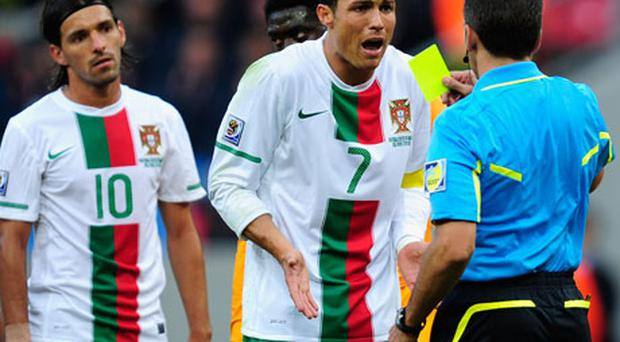 Cristiano Ronaldo looks stunned as he receives a yellow card from referee Jorge Larrionda during the match between Ivory Coast and Portugal. Photo: Getty Images