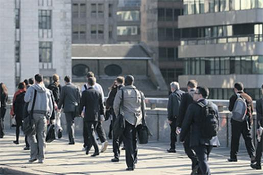 Pedestrians walk over London Bridge towards the City of London yesterday. Job vacancies at London's financial-services companies rose 82pc in the year to May as firms continued to rebuild businesses hurt during the credit crisis