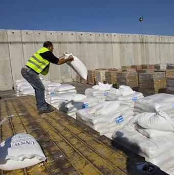 An Israeli worker moves a bag of UN humanitarian aid bound for Gaza as the blockade is eased