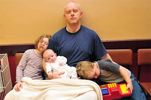 Mark Nixon with his children, Lucy (7), Graham (4), and seven-week-old Scott catch up on some sleep at the local parish hall in Aughnacloy, Co Tyrone, yesterday after their house was evacuated