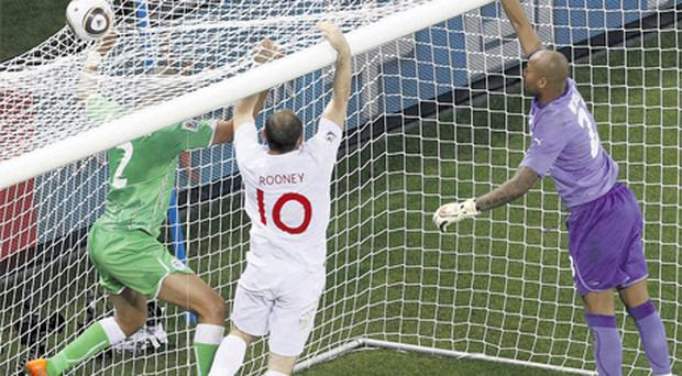 Algeria's goalkeeper Rais Ouheb Mbouli (R), Majid Bougherra (L) and England's Wayne Rooney react just after the ball goes over the bar