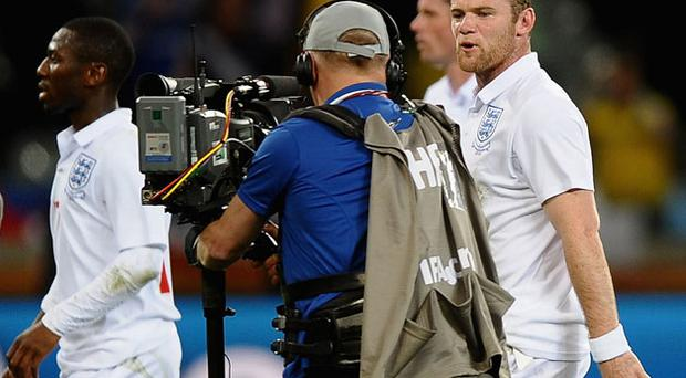 Wayne Rooney speaks to a cameraman as he walks off the pitch dejected after the match between England and Algeria. Photo: Getty Images