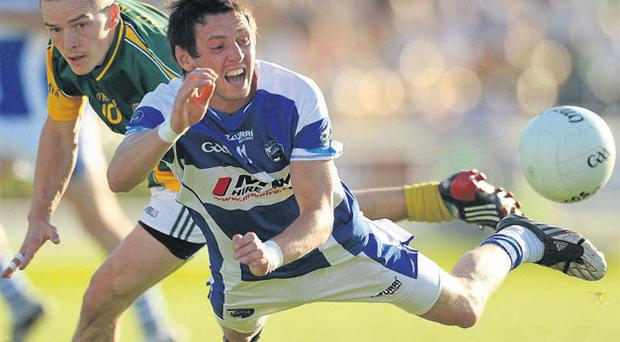 Craig Rogers of Laois goes down under pressure from Meath's Seamus Kenny in Tullamore last night. Photo: Paul Mohan