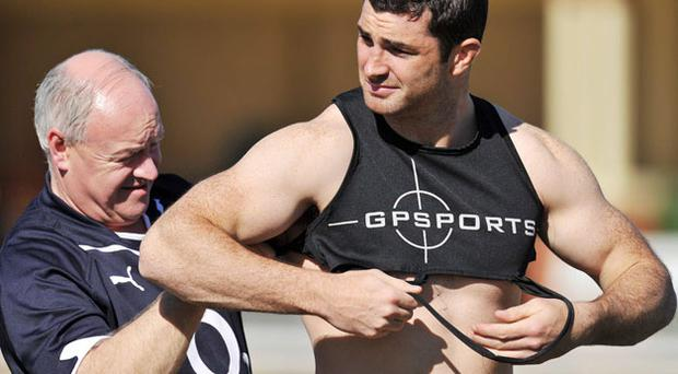 Rob Kearney gets his monitor strapped up by Willie Bennett before Ireland's training session in Brisbane yesterday.