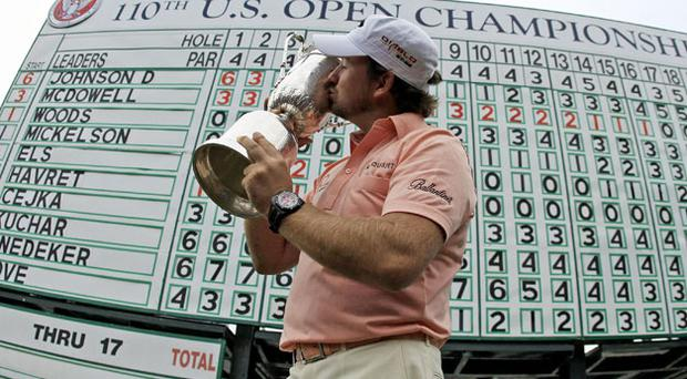 Graeme McDowell kisses the US Open trophy in front of the final scoreboard at Pebble Beach. Photo: AP