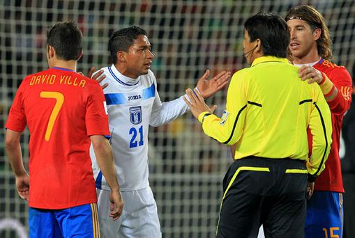 Referee Yuichi Nishimura speaks with Emilio Izaguirre (C) after he appeared to be struck in the face by David Villa. Photo: Getty Images