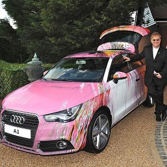 Sir Elton John with a car spin painted by artist Damien Hirst for charity