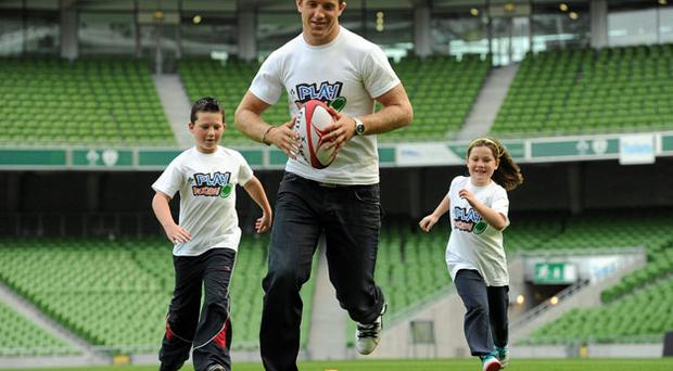 Luke Fitzgerald shows Sinead Cunningham (7) and Darragh Whelan (9) how it's done at the launch of the IRFU's 'Play Rugby' schools and clubs initiative. Photo: Paul Mohan / Sportsfile
