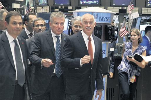 George Papandreou, Greece's prime minister, center, tours the floor of the New York Stock Exchange with Duncan Niederauer, chief executive officer of the NYSE Euronext, left, in New York, earlier this week
