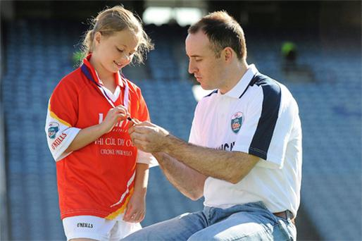 Megan Collins, 10, from Baltimore, Co Cork shows her medal to Tipperary's All-Ireland hero Eoin Kelly