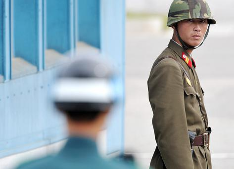 A North Korean soldier, right, and a South Korean soldier stand on duty at the truce village of Panmunjom in the demilitarized zone separating the two Koreas. Photo: Getty Images