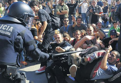 Riot police confront demonstrators in Barcelona yesterday