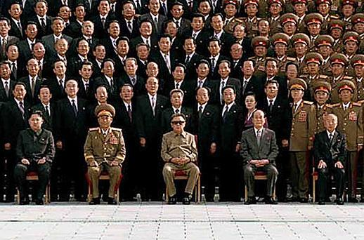 The man two seats away from the North Korean leader is believed to be Kim Jong-Il's son, Kim Jong-Un. The original caption did not name the son, Jong-Un, but KCNA said in a report that Jong-Un had attended the photo session