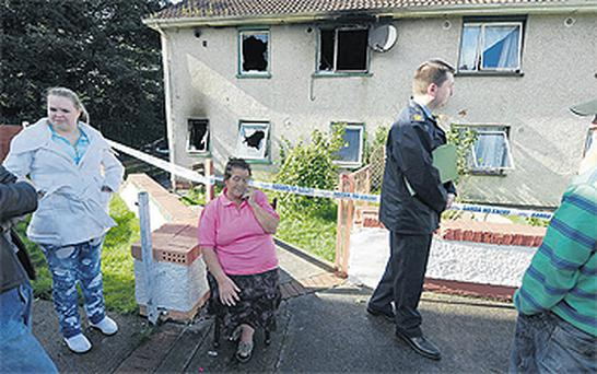 Ann Joyce (centre) sits outside her Longford town home, which was petrol bombed