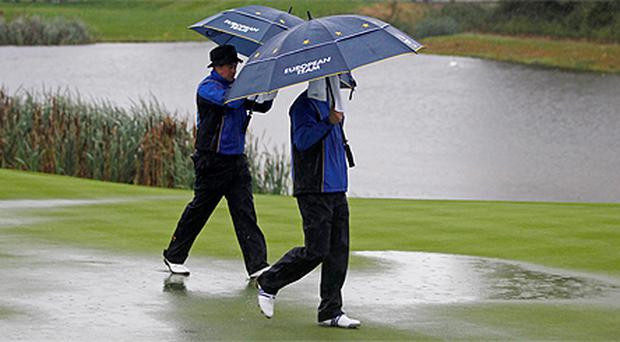 Lee Westwood (left) and Ross Fisher shelter from the rain as as they walk onto the third green during four-ball play on the first day of the 2010 Ryder Cup at Celtic Manor yesterday