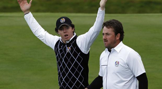 Rory McIlroy gestures to the crowd as he leaves the 15th hole with team-mate Graeme McDowell at Celtic Manor yesterday. Photo: Reuters