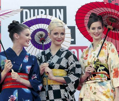 Models Jennifer Foley, Teo, and Isabelle Traber wearing kimonos from the Japanese shop Cactus during the outdoor fashion show on Grafton Street in Dublin and (below) Isabelle in a camel coat from Dunnes. ARTHUR CARRON/COLLINS