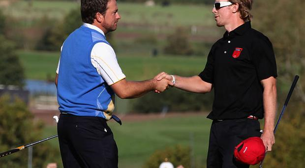 Graeme McDowell shakes hands with Hunter Mahan (R) after securing victory for the European team. Photo: Getty Images