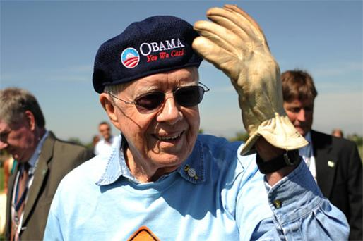 Former US President Jimmy Carter dons his cap with the Obama logo