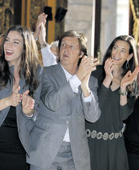Paul McCartney applauds with his girlfriend Nancy Shevell, right, and actress Liv Tyler. THIBAULT CAMUS