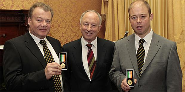 Justice Minister Dermot Ahern presents David Carey and his son Timmy Carey from Blackwater Search and Rescue Diving Club with long service medals at a special awards ceremony at the Shelbourne Hotel in Dublin. Photo: PA