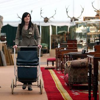 Stephanie Cliffe wheels away a Marmet canvas pram at valued at £15, the cheapest item in the Chatsworth Attic Sale