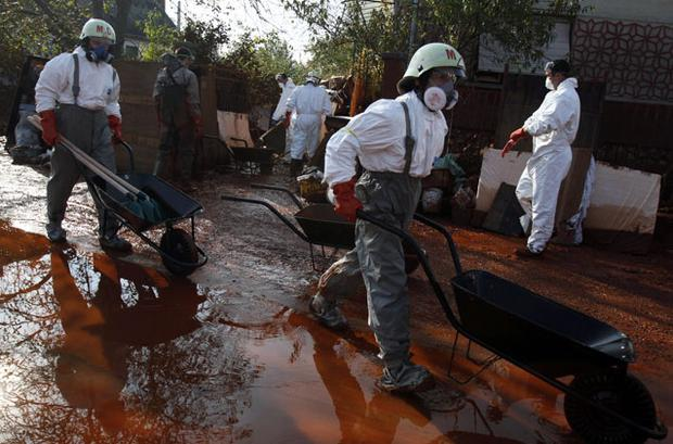 Rescue workers walk in toxic sludge in the village of Devecser, Hungary