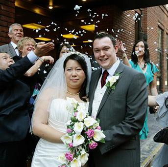 Steven Higham and Ngaryan Li celebrate after their wedding at Manchester Register Office on 10/10/10