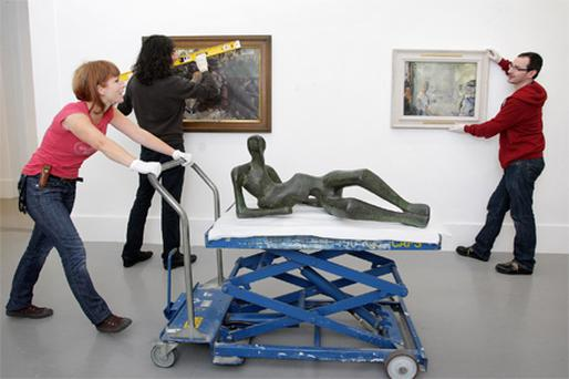 Art technician Antoinette Emoe pushes the 'Reclining Figure No 2' by Henry Moore, as her colleagues Mark Brehan and Graham Cahill hang Jack B Yeats's paintings 'The Small Ring' (1930) and 'Ball Alley' (1927) at the Irish Museum of Modern Art