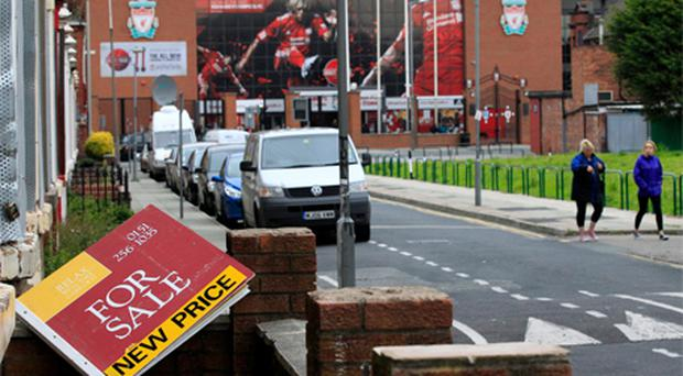 An estate agent's board lies in the garden of a house near the Kop of Liverpool football club as a sale moved closer yesterday