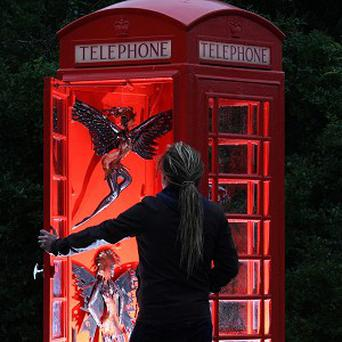 Gallery curator Nick Edell peers into The Phone Box Gallery, in Prickwillow, Cambridgeshire